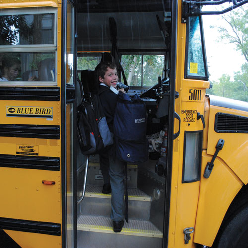 A day student boards the bus to TCS